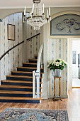 Foyer with white and blue wallpaper, curved staircase and bouquet in silver vase on plant stand