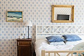 Double bed with white wooden headboard in rustic bedroom with picture and gilt-framed mirror on white and blue patterned wallpaper
