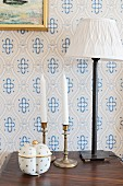 Ceramic pot in front of white candles in candlesticks and table lamp on bedside cabinet against white and blue patterned wallpaper