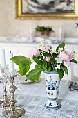 Silver candlesticks and posy in white and blue vase on table