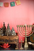 Collection of various religious symbols against pink wall