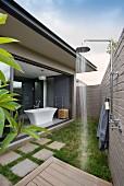 Aussendusche in schmalem Patio, gegenüber offene Glasschiebetür zu Designerbad mit freistehender Badewanne
