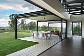 weiße Designerstühle um Tisch auf überdachte Terrasse eines Architektenhauses
