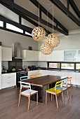Wooden chairs with colourful backrests and seats around table in white fitted kitchen with spherical pendant lamps