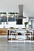 Bar stools at free-standing island counter below extractor hood in open-plan designer kitchen
