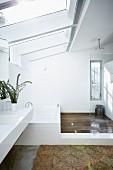 Weisses Designerbad, seitlich Waschtisch mit anschliessender Badewanne in bodenebenem Duschbereich, grosszügiges Oberlicht