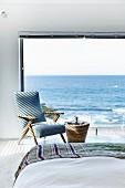 Blick vom Bett auf Panoramafenster mit Meeresaussicht, Sessel im Fiftiesstil