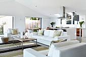 weiße Sitzgarnitur mit Kissen um filigranen Couchtisch, auf Streifenteppich in modernem Wohnzimmer