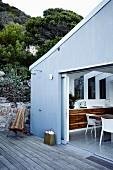 Blick von Holzterrasse mit Aussendusche in offene Küche mit Essplatz
