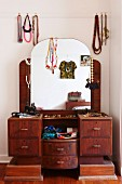 Retro dressing table with arched mirror decorated with necklaces, silk scarves, jewellery and feminine accessories