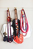 Various necklaces hung from hooks on white picture rail