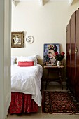 Bedroom with white bedlinen on bed and portrait of artist Frida Kahlo