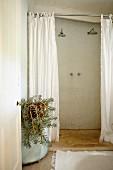 Blick durch offene Tür ins ländliche Bad mit bodenebener Dusche, weisse Duschvorhänge, seitlich Pflanzbehälter mit Sukkulente
