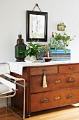Antique lantern, stacked books and potted plants on chest of drawers with partially visible classic chair to one side