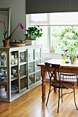 Delicate metal chair at rustic wooden table next to half-height, glass-fronted cabinet