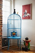 Pale blue, retro birdcage next to garden gnome and window in corner