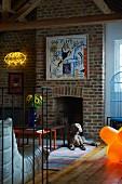Bild und Kunstobjekt an Ziegelwand mit offenem Kamin, davor Hund am Boden liegend