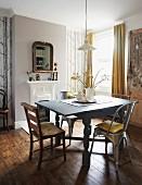 Stühle aus Holz und Metall um hellgrau lackierten Holztisch mit gedrechselten Beinen in traditionellem Esszimmer