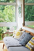 Scatter cushions and grey seat cushions on fifties bench next to glass wall with view into garden