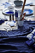 Dyed fabrics, papers, containers of indigo dye and painting utensils on craft table