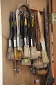 Various paintbrushes and fretsaw in carpenter's tool cabinet