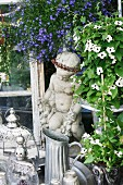 Stone statue & decorative vessels surrounded by summer flowers
