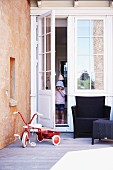 Vintage tricycle and outdoor furniture on wooden deck; child standing in open glass door