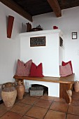 Comfortable bench with scatter cushions around masonry corner stove