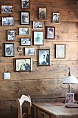 Framed family photos on wooden wall behind vintage table lamp on table