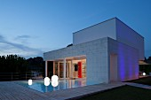 Twilight atmosphere; pool, spherical floor lamps and wooden deck outside contemporary house