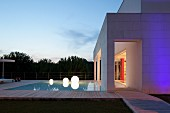Twilight atmosphere; pool and spherical lamps outside contemporary house