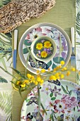 Floral crockery, table runner and sprig of yellow flowers viewed from above