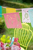 Romantic bunting with perforated bird motifs above pink cutlery basket in garden