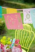 Romantische Girlande mit Vogelmotiv über pinkfarbenem Besteckkorb im Garten