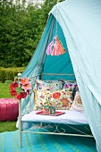 Metal bench with cushions in pale blue tent in garden