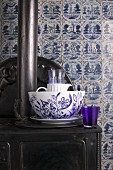 Blue and white crockery on antique cast iron stove against old wall tiles in classic Delft blue and white