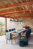 Dining area below bamboo pergola; blue blankets, lamps and tealight holders on suspended wooden board