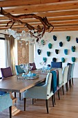 Dining room with comfortable armchairs and lamp made from branch; masks on wall, armchairs and accessories in various shades of blue