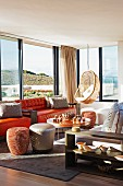 Various seats such as hanging chair, sofa and pouffes in lounge area with view through panoramic windows