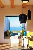 Matratze und Kissen vor Panoramafenster mit Meerblick