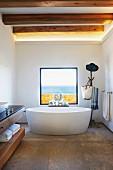 Freistehende Badewanne vor Panoramafenster mit Meerblick im Designerbad