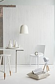 Simple stool dipped in white paint and cushion on floor in front of modern chair around dining table