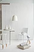 Schlichter Hocker in weisse Farbe getaucht, Kissen auf Boden vor modernem Stuhl um Esstisch