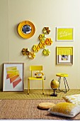 Still-life arrangement of small, yellow table and yellow-painted, retro chair below cake tins and pictures on pastel yellow wall