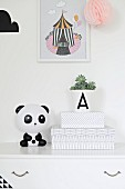 White box with graphic pattern and panda ornament on white chest of drawers below picture with circus motif on wall