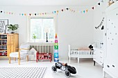Spacious child's bedroom with colourful bunting, retro toy car, red doll's bed and white cot