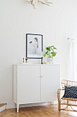 White, half-height cabinet, black-framed picture and wicker armchair with black and white scatter cushion