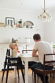 Father and child in high chair at white dining table below crystal chandelier