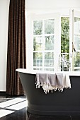 Cloth hanging over edge of free-standing vintage bathtub in front of half-open balcony door