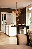 Modern pendant lamp above dining table and white upholstered chairs in brown-painted interior with traditional ambiance
